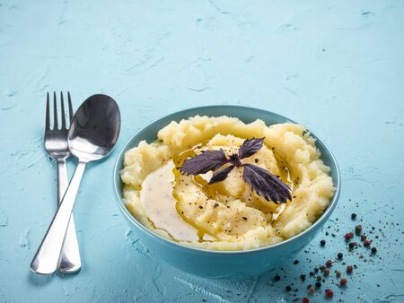 Mashed potatoes with fresh red basil, peppers and olive oil in blue bowl on blue concrete background. Copy space. Banco de Imagens