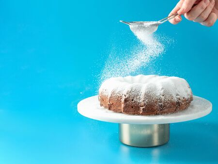 Womans hand sprinkling icing sugar over fresh home made bundt cake. Powder sugar falls on fresh perfect bunt cake over blue background. Copy space for text. Ideas and recipes for breakfast or dessert