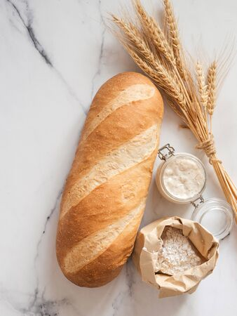 British White Bloomer or European sourdough Baton loaf bread on white marble background. Fresh loaf bread and glass jar with sourdough starter, flour in paper bag, ears. Top view. Copy space. Vertical Stok Fotoğraf