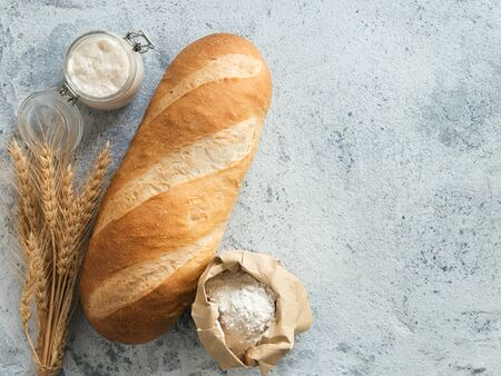 British White Bloomer or European sourdough Baton loaf bread on gray cement background. Fresh loaf bread and glass jar with sourdough starter, flour in paper bag and ears. Top view. Copy space