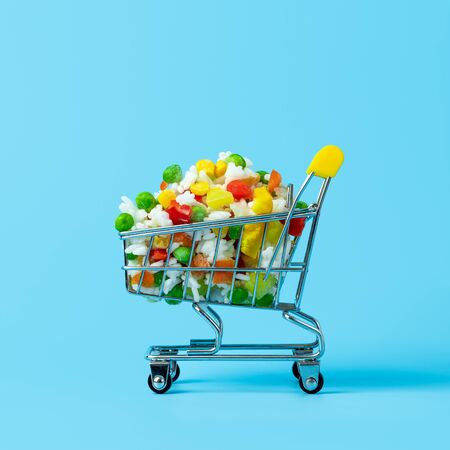 Frozen vegetables assorted in toy shopping cart on blue background. Full of assorted frozen vegetables food shop trolley. Square crop