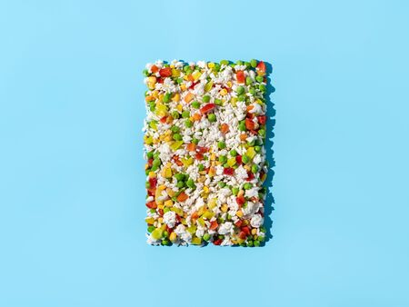 Frozen vegetables assorted on blue background. Assorted frozen vegetables food with ice, top view or flat lay. Raw uncooked frozen hawaii mix. Hard light.