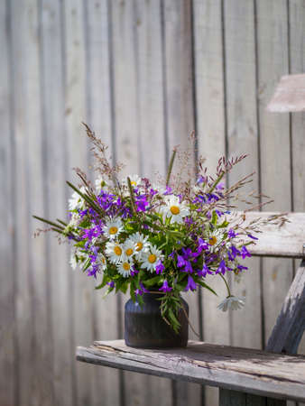 Bouqet with wild flowers on old wooden bench. Field flowers bouqet with campanula and camomile. Cottagecore and farmcore concept. Copy space