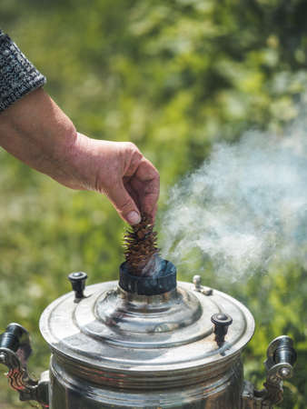 Woman hand hold cone fir near vintage smoking Samovar, the traditional russian water boiler. Fire up samovar outdoors. Vertical. Copy space for text or design.