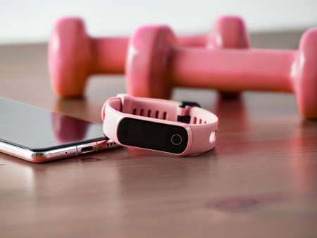 Fitness tracker on smartphone and pink colored dumb-bell on wooden tabletop. Pink female pedometer or wearable device on smartphone with infinity display, copy space