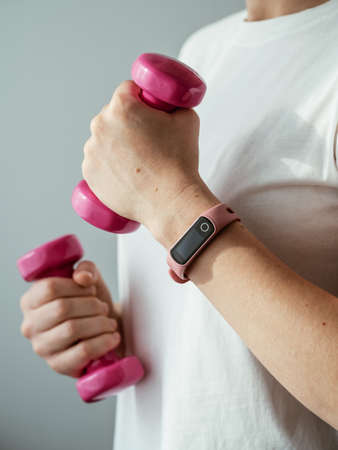Unrecognizable young woman in white shirt with pink wearable device and bright pink colored dumb-bell in hands. Focus on pink fitness tracker on female hand. Hands with barbells. Vertical