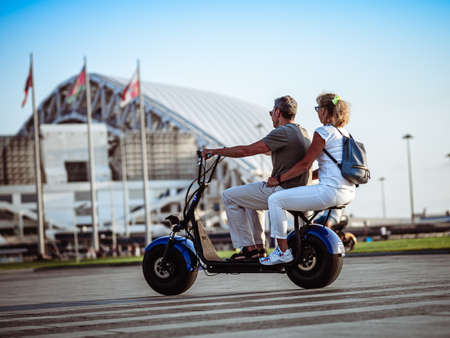 Man and woman on two-seater electric scooter Éditoriale