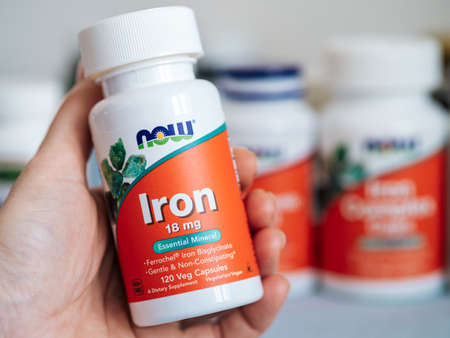 Jar with Iron by Now Foods capsules in female hand