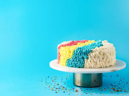 Colorful shag cake on blue background, copy space