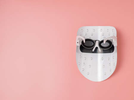 Led light face mask on pink background, copy space Stock fotó
