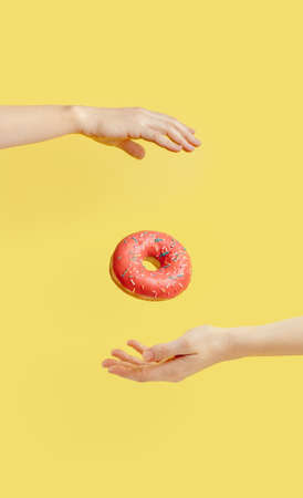 Donut falls between hands on yellow background Stock fotó