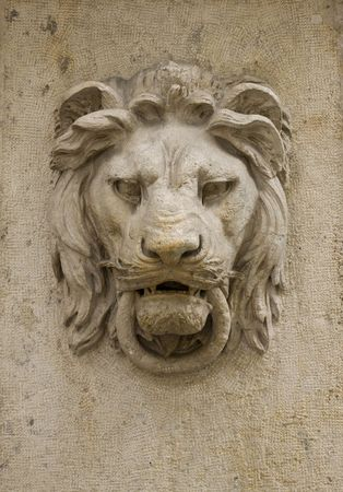 stone lion: Architectural detail of a lions head on the wall of a building