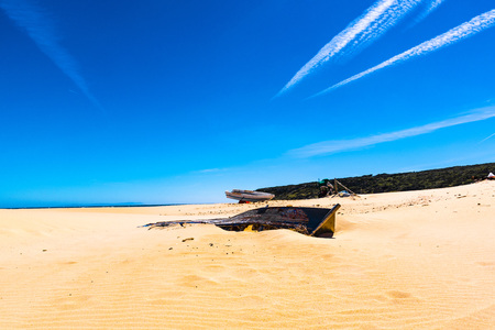 wooden boat abandoned on a beach for the future memory of a desertification that moves inexorably