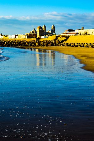 sunset over the Ocean in Cadiz in Spain, with a splendid golden light and city 写真素材