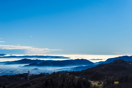 breathtaking view to Tretto di Schio, Italy, in the background the Po valley with the typical spring fog and an isolated campground id a forgotten village 스톡 콘텐츠 - 124984199