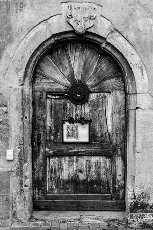 old wooden door set on a stone frame with a rusty metal frame