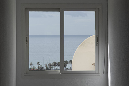 white closed window with round object and horizon on the sea with palm trees