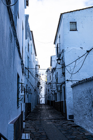 one of the most evocative pueblos blancos in the evening at Casares in Spain, tinged with blue tones Фото со стока