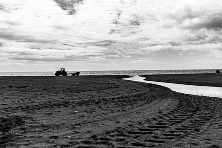 tractor arranges the beach before the tourists arrive in Estepona Spain, in the background the Mediterranean sea. black and white forotgrafia Banco de Imagens