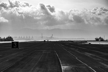 airstrip of an airport that ends at the port in the Gulf of Gibraltar Stock Photo