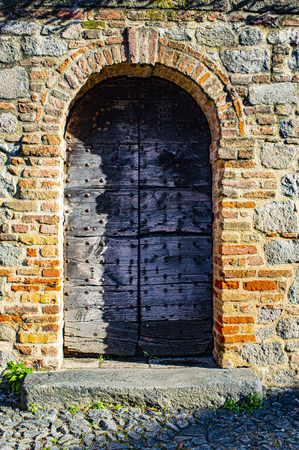 wonderful wooden door set in Mantuas medieval walls with brick walls and a stone arch Фото со стока