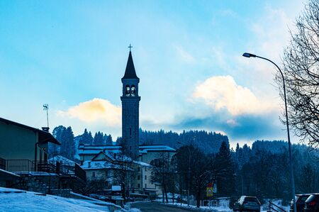 the small town of Tresche Conca on the Asiago plateau illuminated by the sunset turns into a blue with mysterious traits