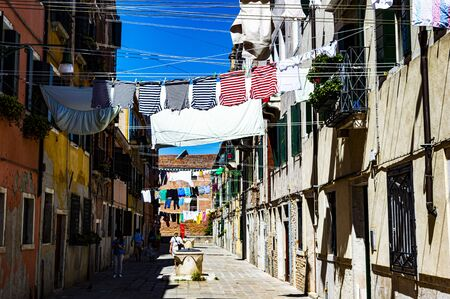 gondolier shirts hung out to dry together with the rest of the linen in a calle of veneziua during the contemporary art biennial and a blinding sun Stock Photo - 124984576