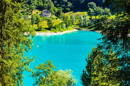 beautiful photograph of Lake Tenno in Trentino Alto Adige, on a sunny day, where the water of a crystalline green is reflected