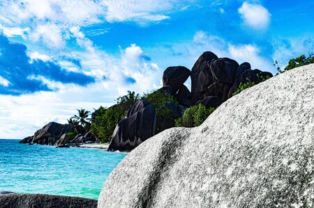 monolith of granite in the foreground blocks the gaze of a paradisiacal beach in the Seychelles with a crystal clear sea and a blue sky 写真素材