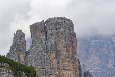 mountaineers climb the pinnacles of the dolomites in the background