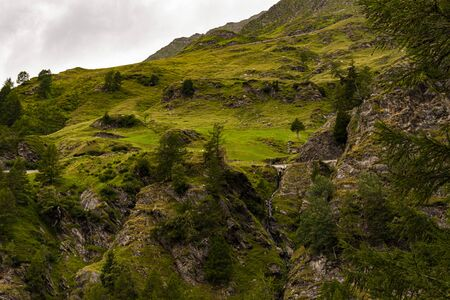 Photo of Passo rombo on a gloomy day in August with river meadows, pines, pebbles and breathtaking views, blue green colors