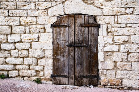 close vintage wooden door set in a stone wall of an ancient farmhouse