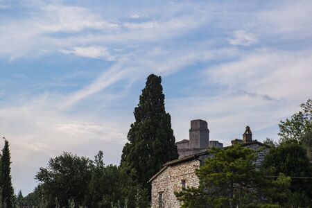 beautiful image of the towers of Assisi with blue sky and white clouds Фото со стока - 131088403