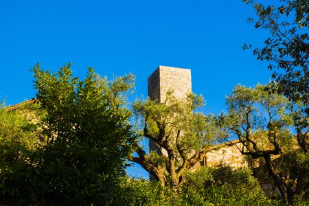 medieval tower in stones over the hill with olive trees and blue sky in the hills of Umbria Italy Banco de Imagens