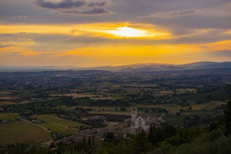 image of the Basilica of San Francesco in Assisi with a splendid sunset laden with orange and red colors with a view of the Umbria Italy plain