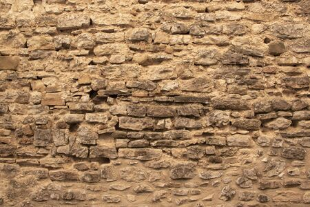 ancient wall of stones and mortar with bricks and wood