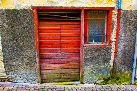 vintage red wooden door with red window with grating and red gutter on gray wall with green moss
