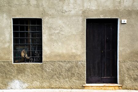 dark wooden door with window with iron grating and carved wood inside vintage glass