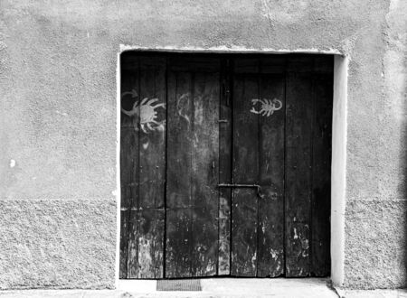 dark wooden door with zodiac signs black and white photos Фото со стока