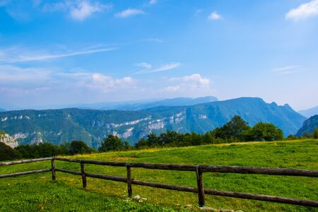 beautiful panorama of the Posina and Astico valleys from malga Zolle di Sopra with the wooden fence in the foreground on a clear summer day in the Italian Alps. 写真素材 - 132897054