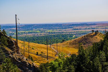 electric cables stand out among the peaks of the Flatirons in Chautauqua Park in Boulder Colorado on a beautiful late summer day with yellow grass and green trees.