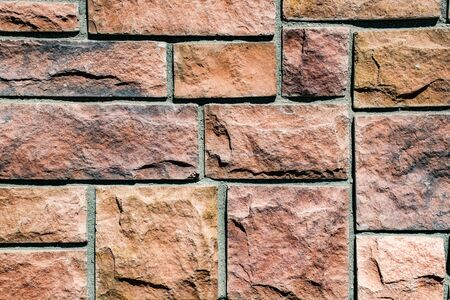 photo of a wall of reddish stone bricks bound by gray cement Stockfoto - 134036829