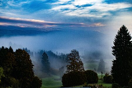 fog rises quietly among the trees and meadows in the beautiful mountains of the Asiago plateau near Vicenza, Italy.