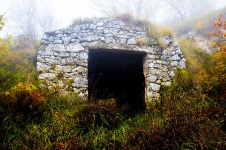 ruin of stone farmhouse shrouded in November fog on the path to Monte Pau in Cogollo del Cengio in the province of Vicenza, Veneto, Italy.