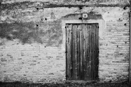 black and white photograph of a wooden door with vintage wall Stockfoto