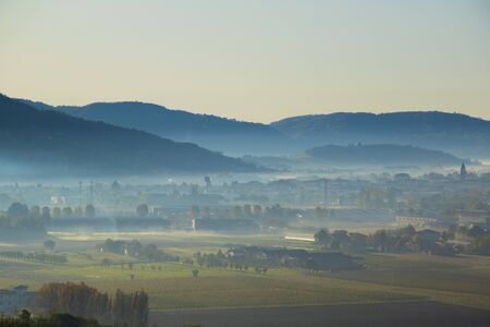 evocative image of autumn fog on a splendid Novemebre day of the plain in front of Sovizzo small town on the hills of Vicenza, Veneto, Italy. Stockfoto