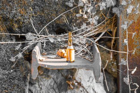 small orange bottle on rusty iron beam set in the rock