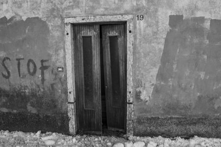 black and white photo of an open vintage door in an abandoned house in Asiago, Veneto, Italy.
