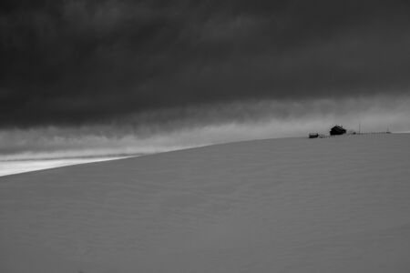 threatening sky looms over the hut between snow-covered meadows on the Asiago plateau, Veneto, Italy.