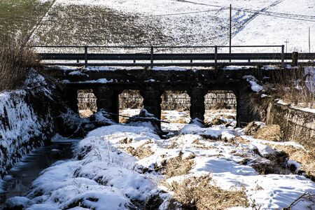 bridge over the snow-covered Ghelpach on a sunny December day in Asiago, Veneto, Italy. Stockfoto